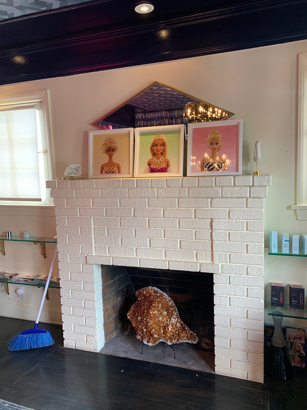 Barbie art hangs above the fireplace for a whimsical touch.