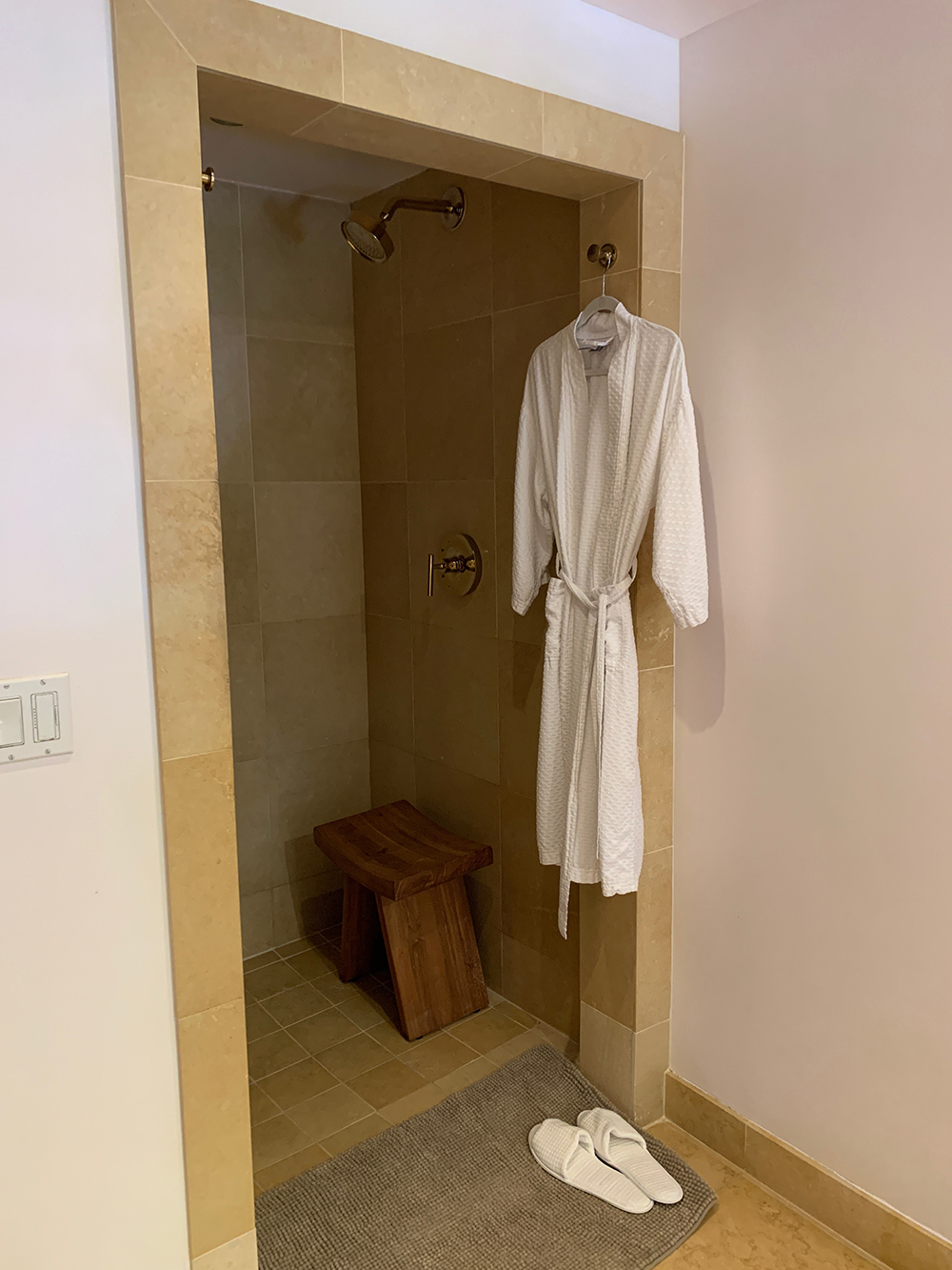 A private shower with robe and slippers.