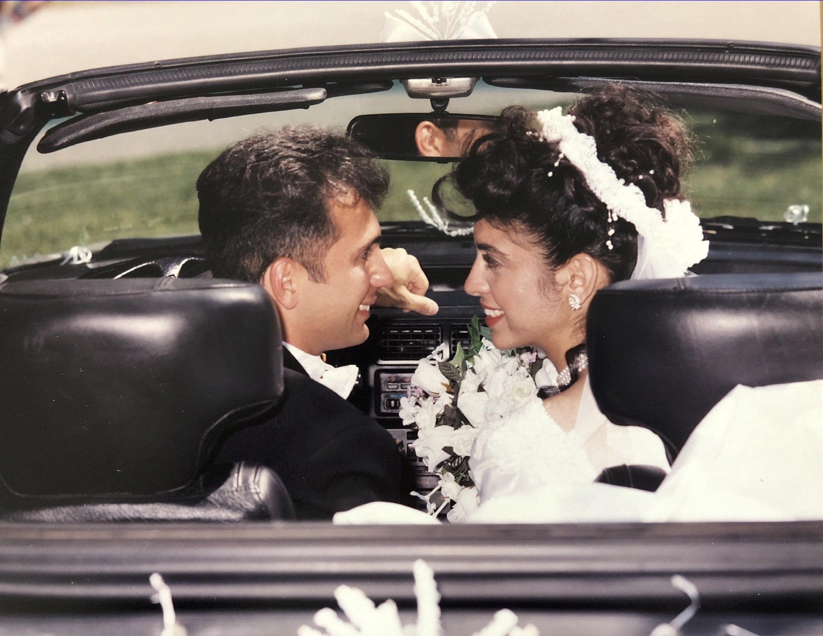 Newlyweds, driving away from the ceremony in a convertible