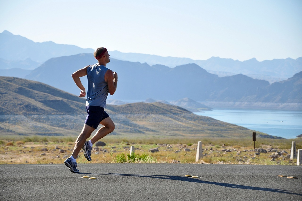 stock photo of running man with mountain and lake in the back