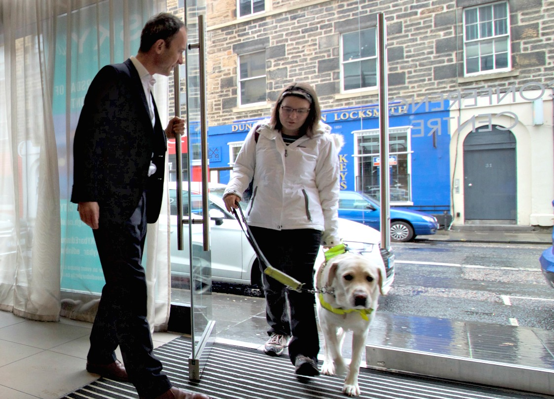 Angela and her guide dog Uffa being welcomed at the door of DoubleTree Hilton