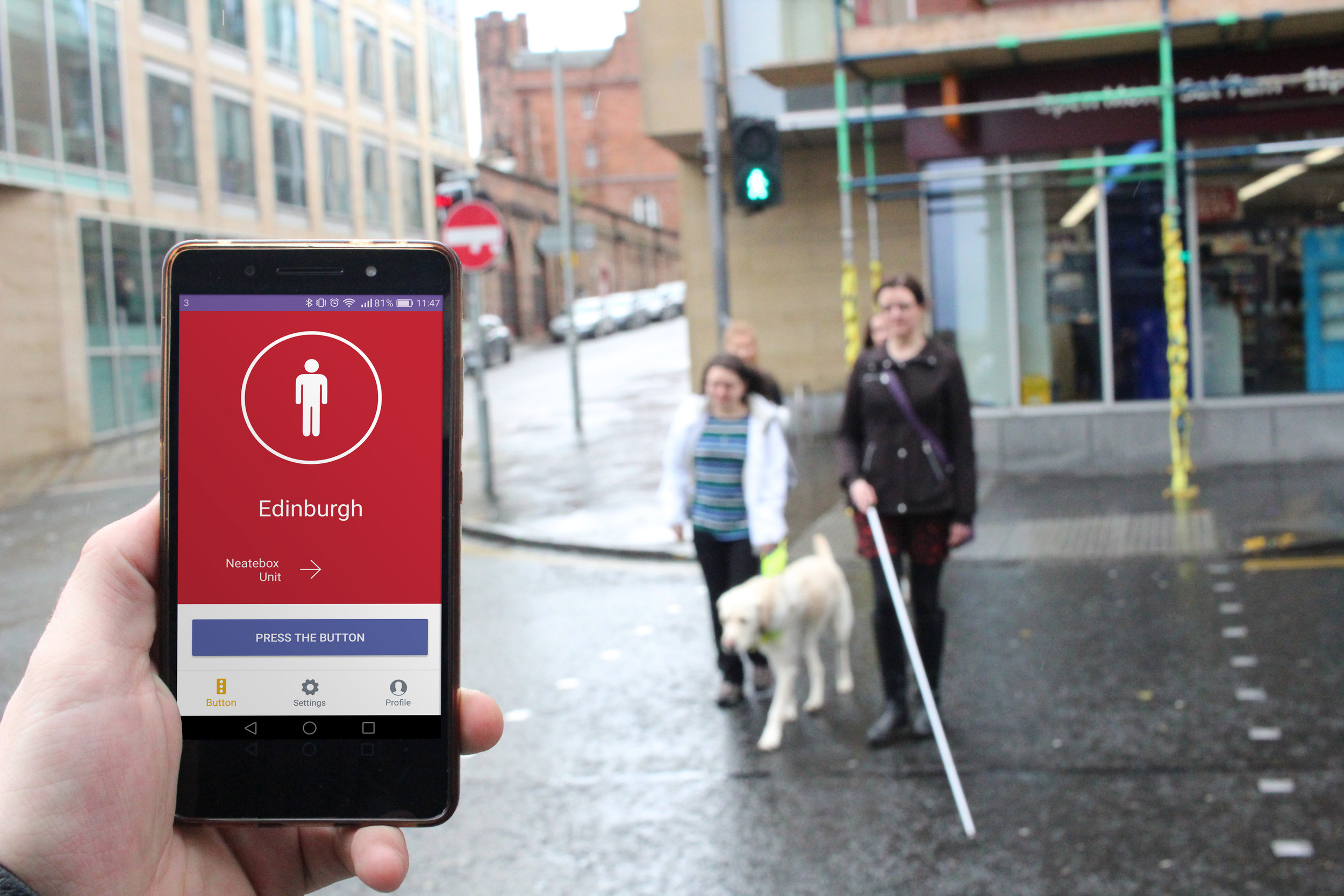Two visually impaired users crossing the street using Button by Neatebox. Photographer is holding phone showing Button connected to the crossing.