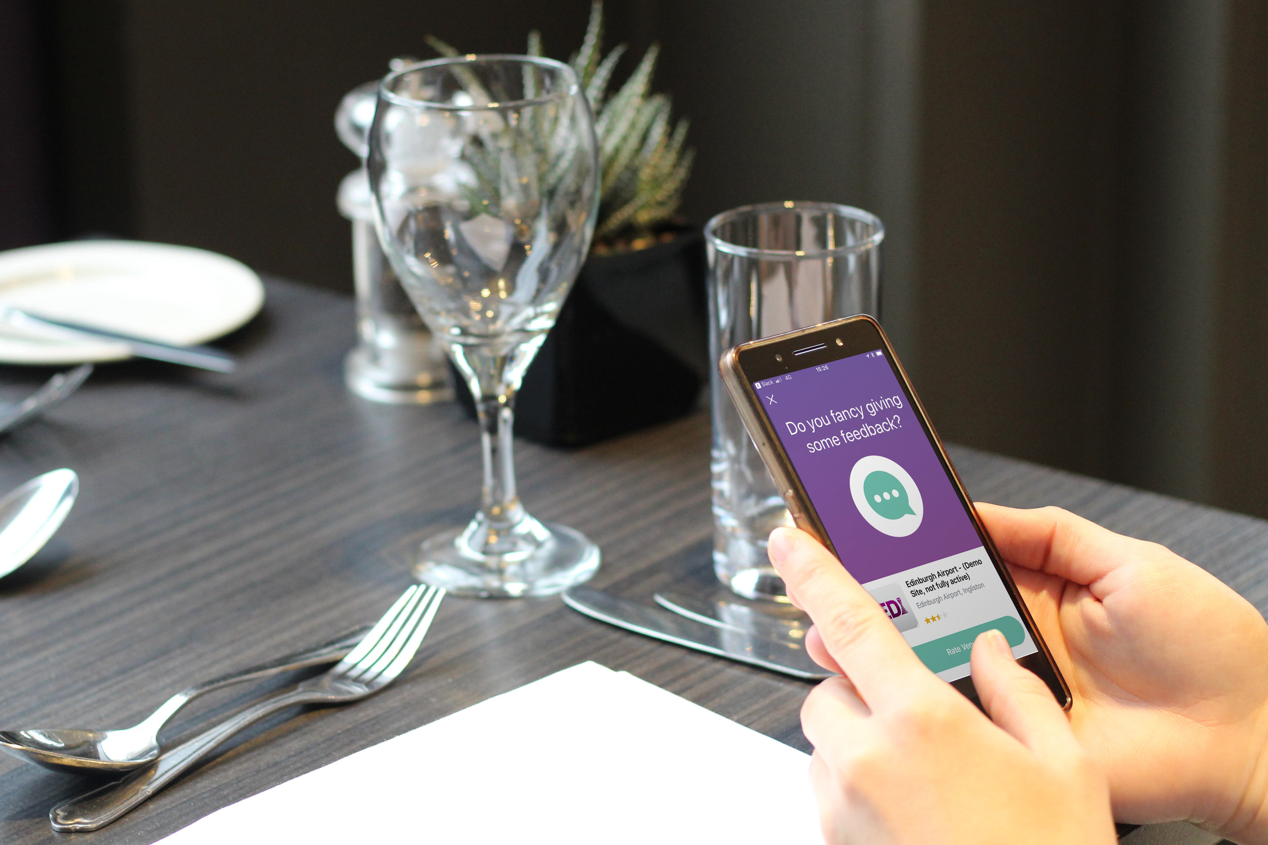 Sabrina sitting at restaurant table leaving feedback for a Welcome venue in the app.