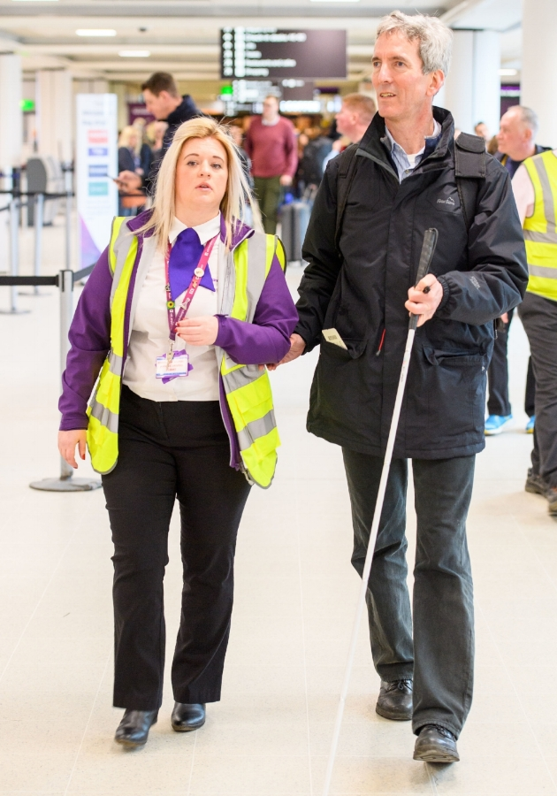 Assistance staff guiding a passenger with disability through the