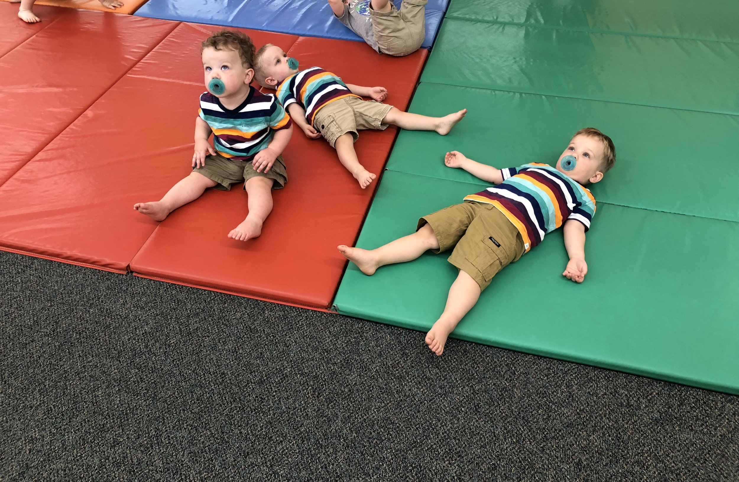 Andrew, Colin and Matthew look up at the parachute at the end of Gymboree class. They are worn out from playing with friends!