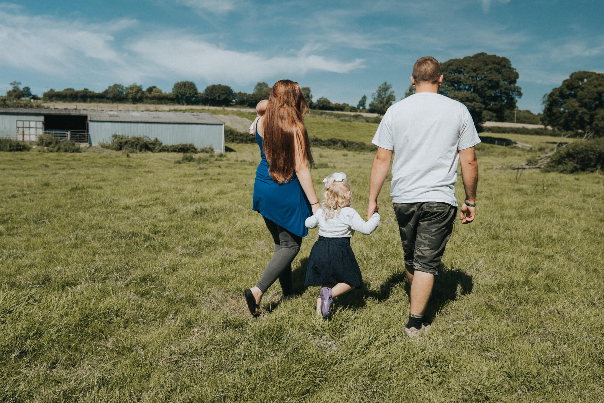 Family session on location, family walking through North Devon farm field