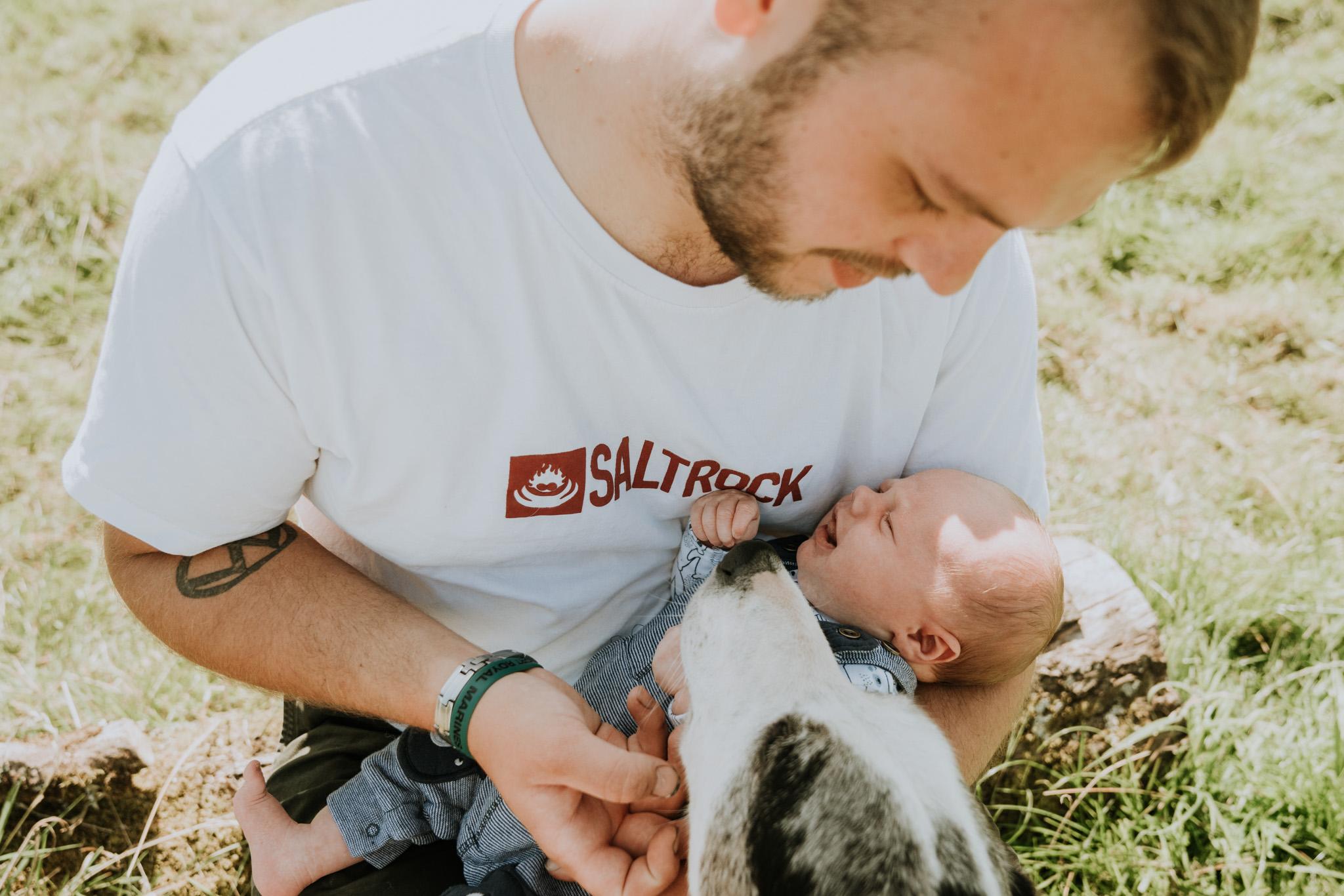 Father, his newborn son and farm dog