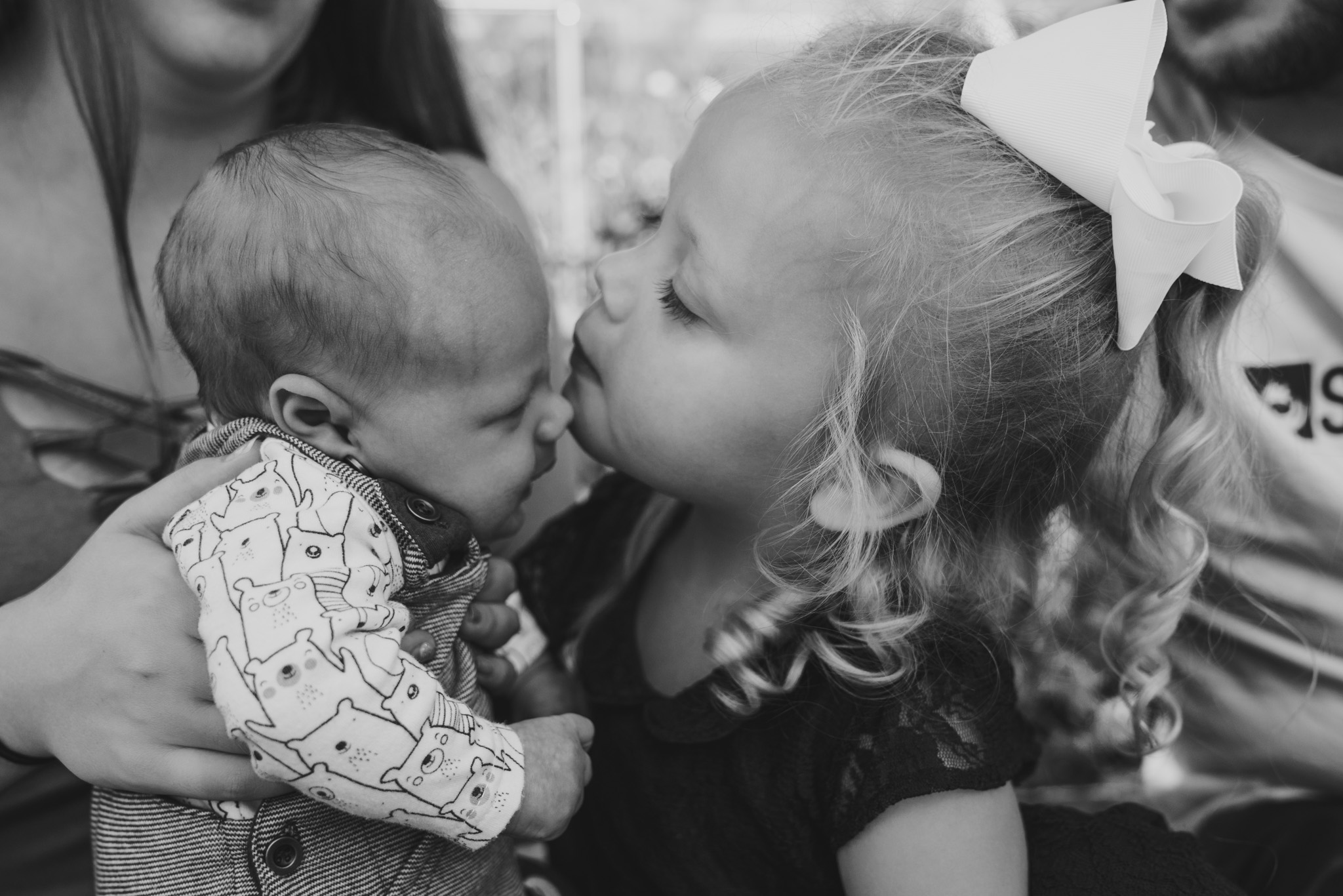 Three month old newborn baby and toddler sister kissing him on forehead at a family session