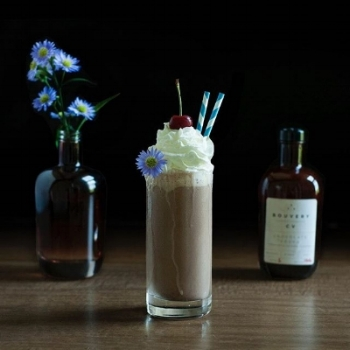 a chocolate drink in a highball glass with whipped cream and blue flowers.