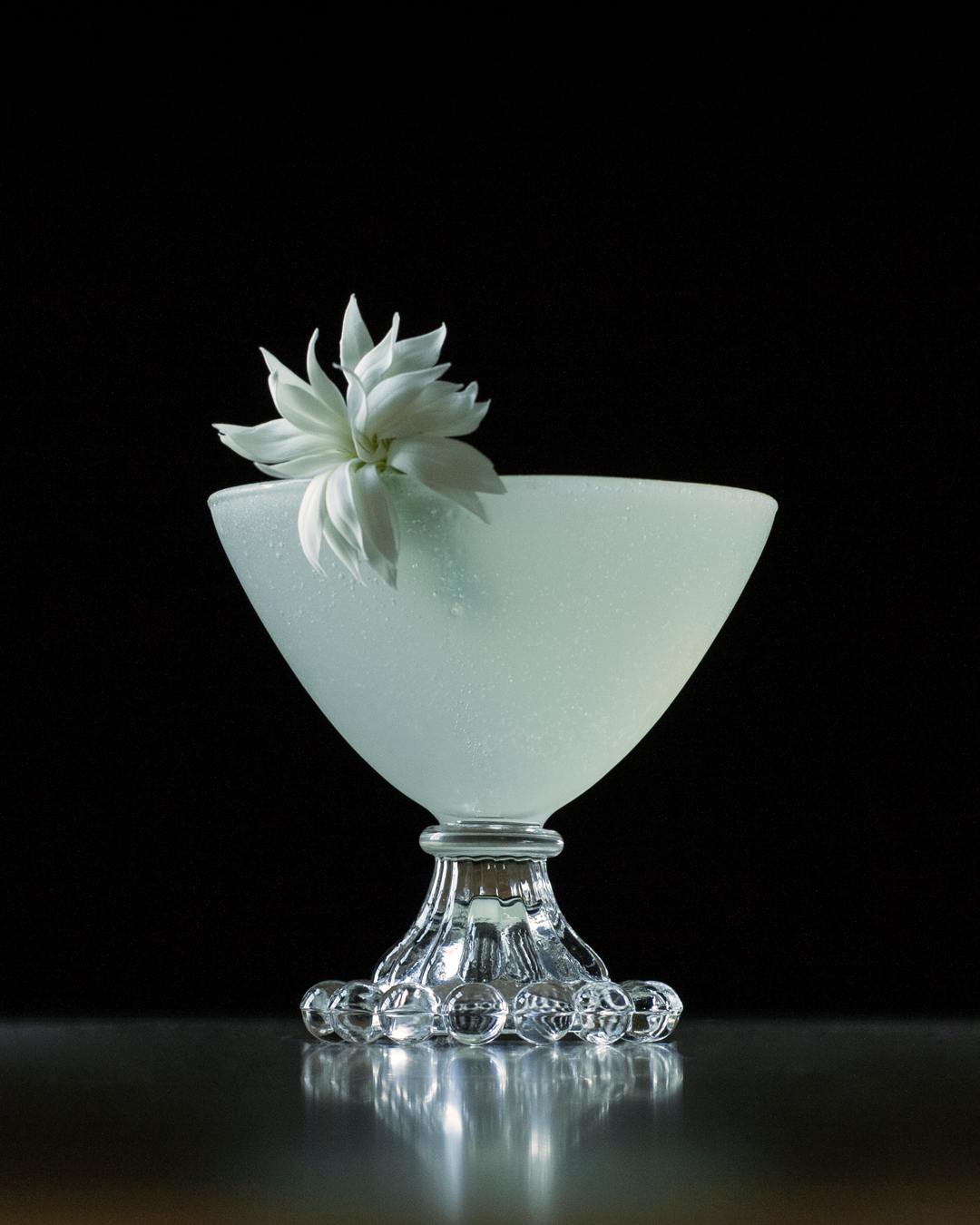 a white cocktail garnished with a white flower