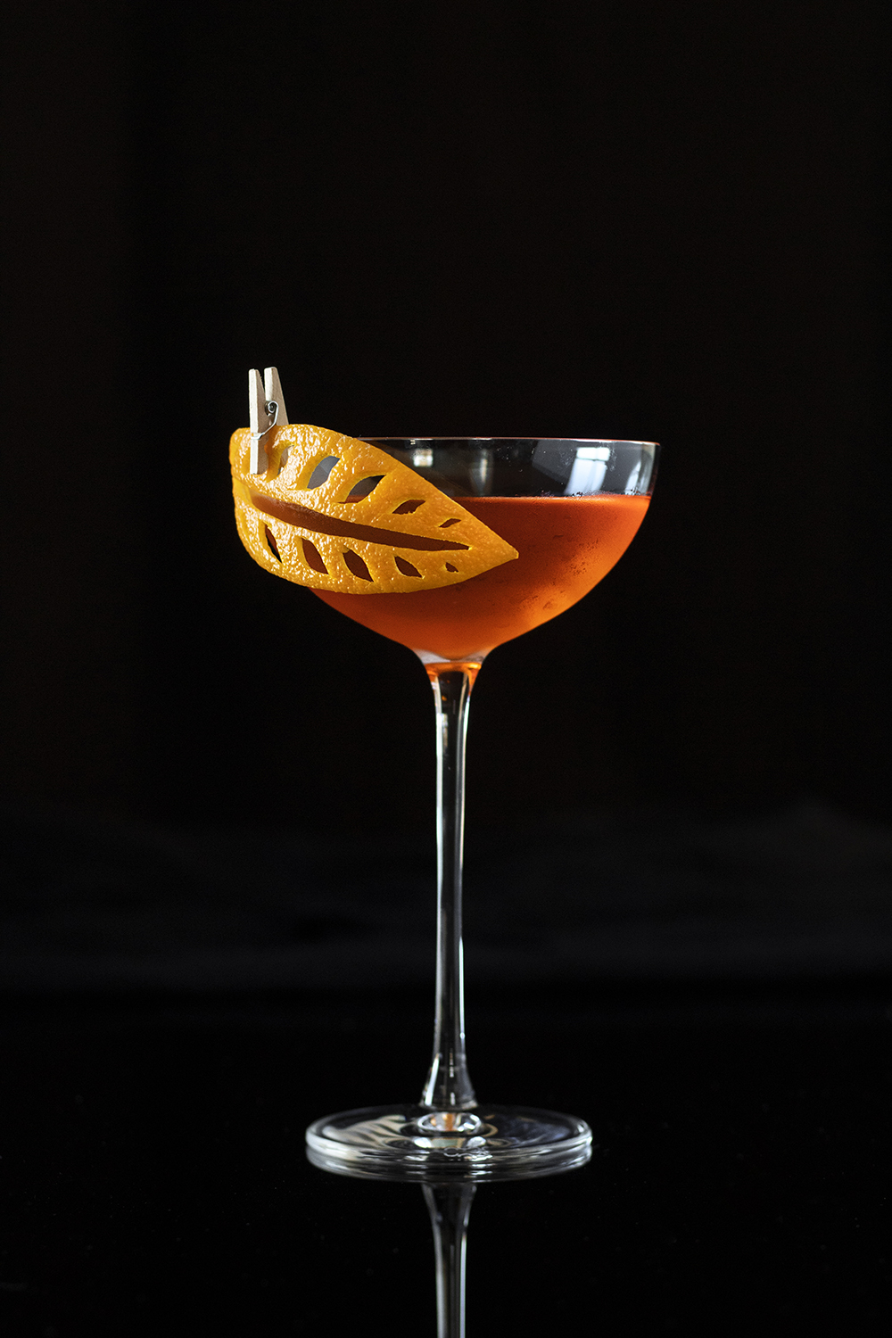 """an orange cocktail in a coupe glass with a carved orange peel """"leaf"""""""