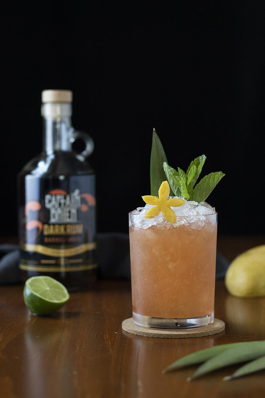 an orange drink in a rocks glass with mint