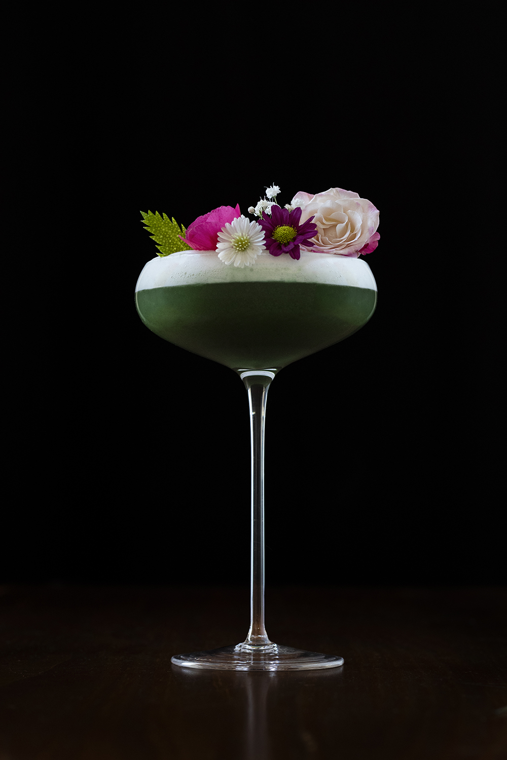 a dark green cocktail in a stemmed glass garnished with many flowers
