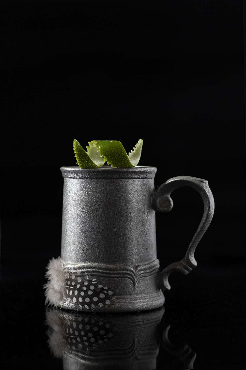 a silver metal mug decorated with a chicken feather and a lime peel