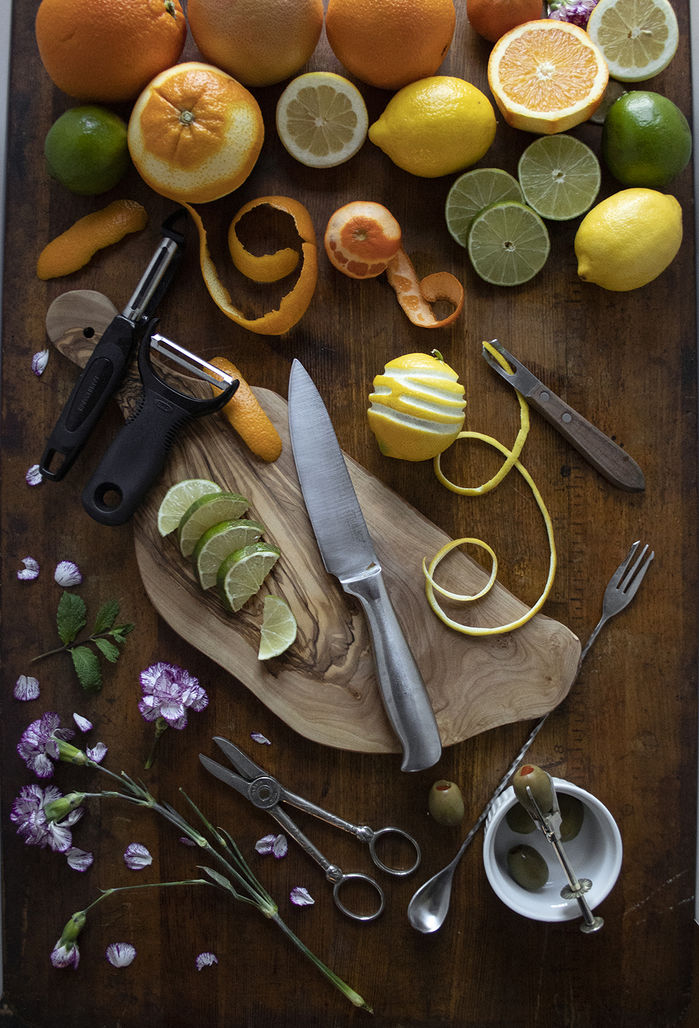 citrus fruits, flowers, and olives on a wooden table