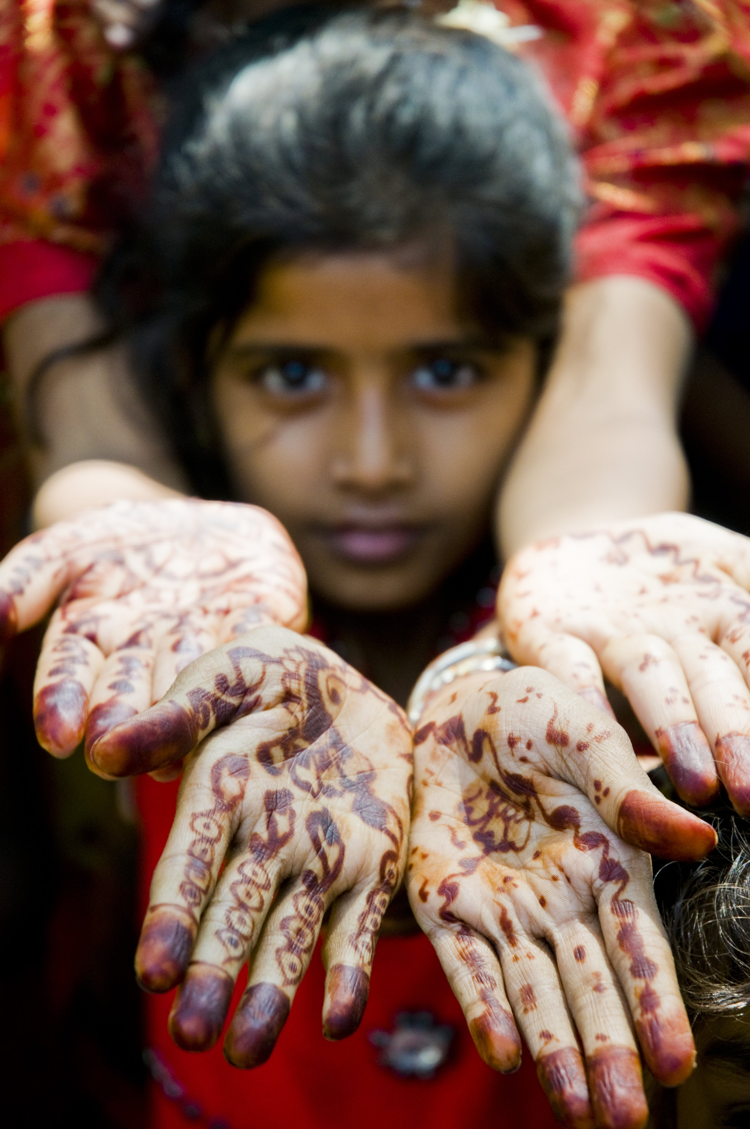 Travel Image ~ Henna Hands - Bombay, IndiaThe city of Bombay bustles with life. North of the city center lies some quiet havens where space exists for your thoughts to abound as the waves of the Indian Ocean crash the shore. This girl and her mother live in one of these quiet havens that erupt into excitement during weddings and festivals. The henna on their hands is temporary but is part of intimate ritual and worn by the bride's family for her wedding. It is the writing of the ancient designs for the well wishes to the bride for a happy marriage and fulfillment of her dreams.