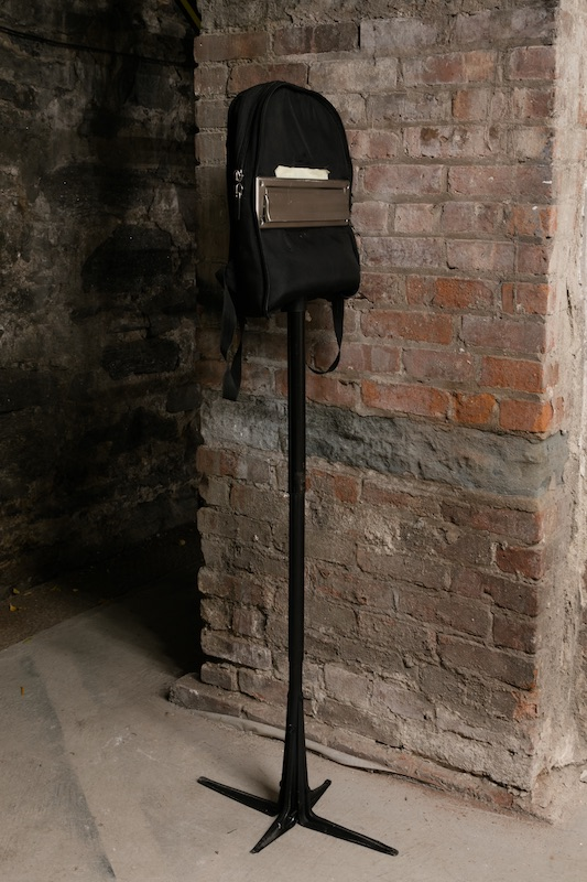 Chris Zacher  Mailbox , 2018 Backpack, mail slot, metal pole, shelf brackets, spray paint, masking tape and hardware 56 x 14 x 3 inches
