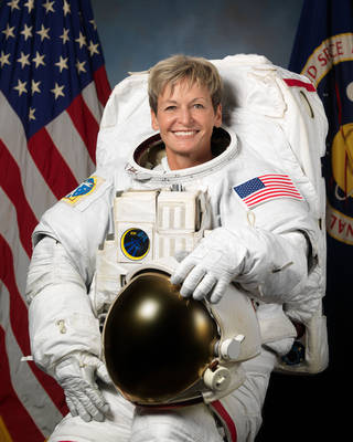 NASA astronaut, Peggy Whitson, sits down in front of the American flag with her spacesuit on. She has her helmet on her lap as she smiles widely for the camera
