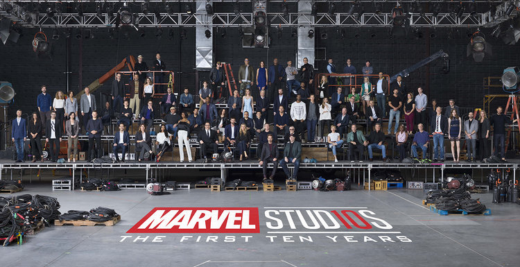 """a group of more than 80 actors and filmmakers gathered on stage to take a photo. """"Marvel Studios The First Ten Years"""" can be read beneath the stage"""