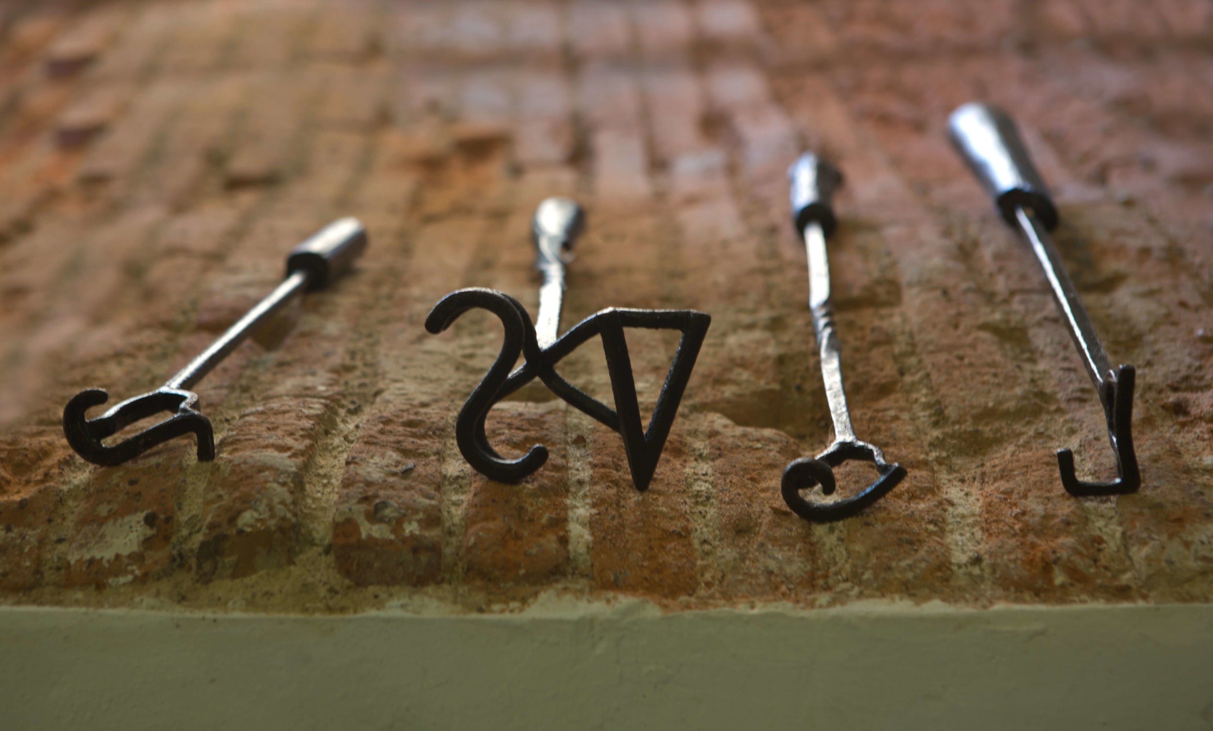Branding irons displayed on brick