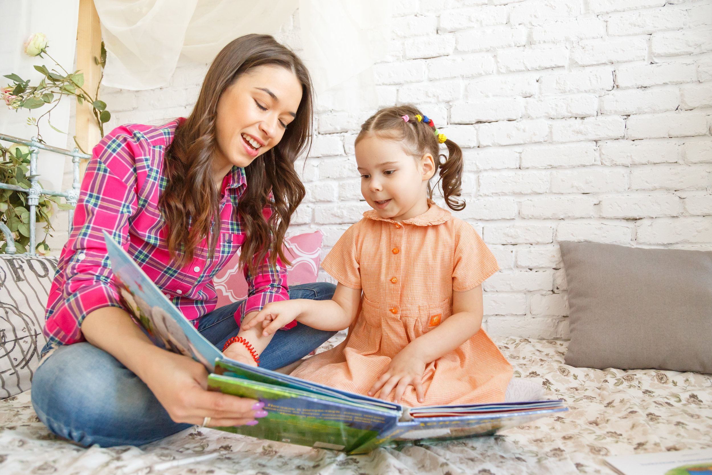young-mother-and-her-child-girl-reading-a-book-PEPCFQR.jpg