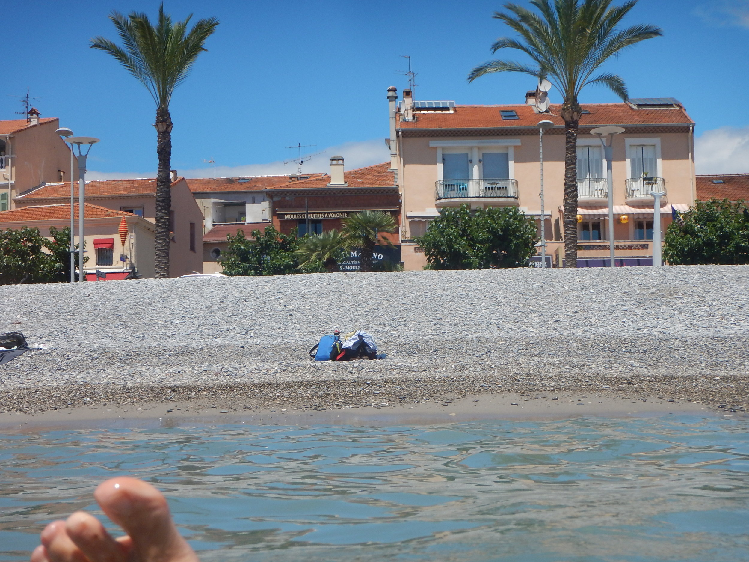 A pebbly beach just across from a cafe strip. My blue bag being minded by Harri.