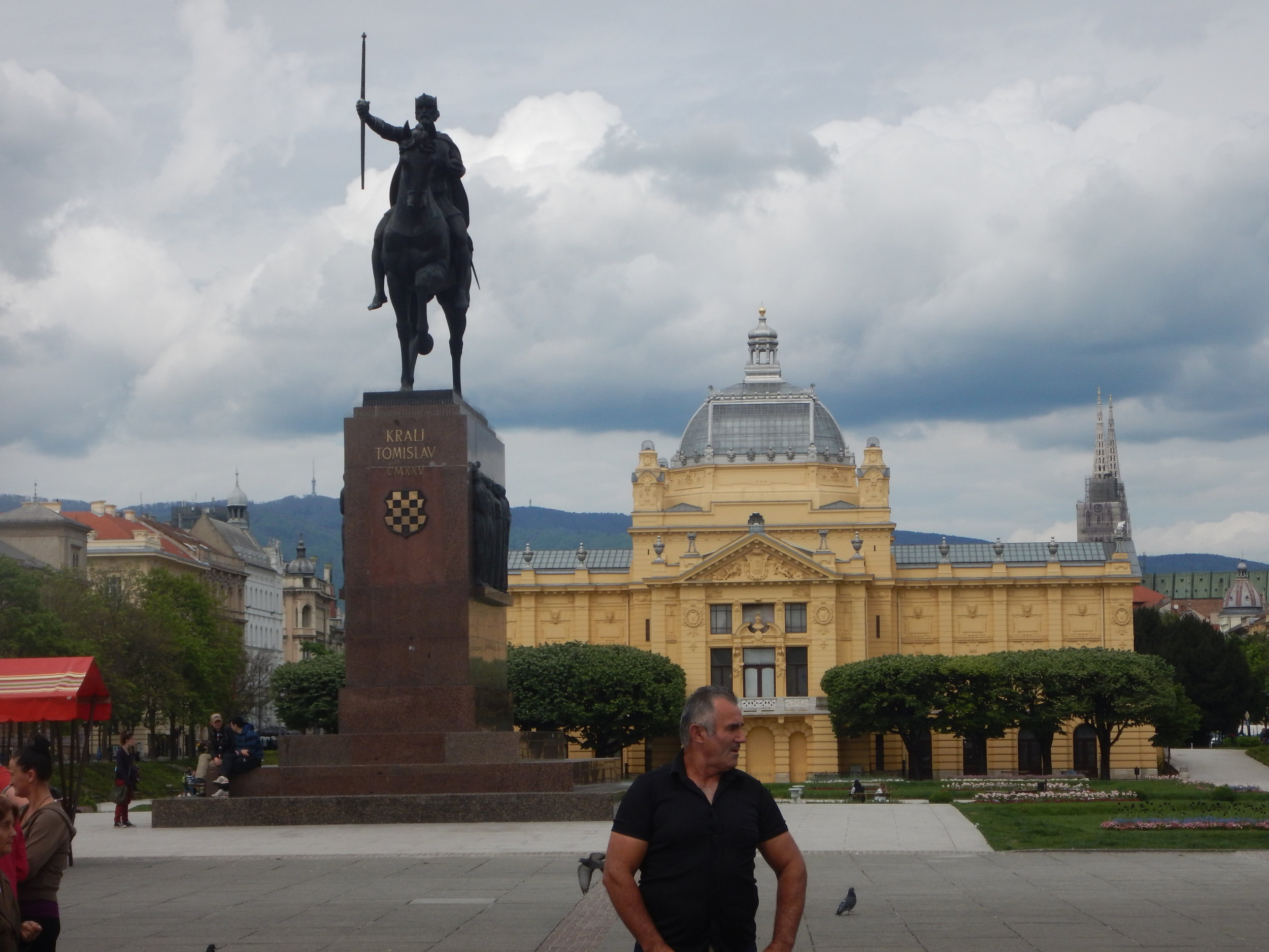 Downtown Zagreb, horizon shows tv transmitter, Tomislav monument, gorgeous old public building in park setting and cathedral spires.