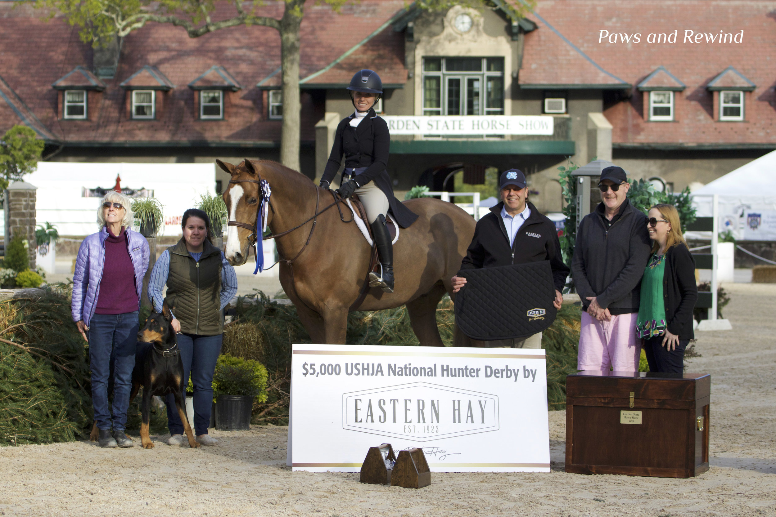 Kathy Kunsman, Eric the Doberman, Lauren Sabo, Eleanor Kunsman and Beckham, Chris Johnson of Eastern Hay, and John and Ashley Buehler with Seahorse Tack Trunks. Photo by Paws and Rewind