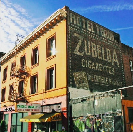 """Larkin at Geary. ZUBELDA CIGARETTES THE DOUBLE PACKAGE – Larkin and Geary – building built in 1909. Hotel Toronto – formerly Leiah Hotel, Wesley Hotel, and Hotel California.  From a 1912 print ad """"'You can't describe her, sighs the Khedive, because there was never anything like her. She's a poem, a little mountain brook, a rose garden, a ----.' The P. Lorillard Company named their new Turkish blend cigarette Zubelda, in honor of the Khedive of Egypt's wife. Lorillard felt that their Zubelda was just like the lady, and claimed 'They taste like shooting stars. And their fragrance is like the Garden of Eden. They're as gracious and welcome as a long-absent sweetheart.' """"  Zubelda cigarettes debuted in October 1912 which would place this sign from around that period.  Packets included a  small oriental rug insert . Assorted Zubelda ads  here  and  here ."""