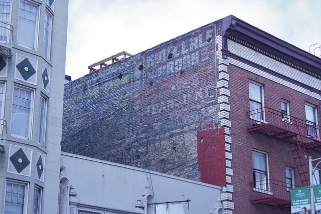 924 Geary. A riot of faded color between two residential buildings on Geary. Two ghost signs are visible here, the lower one the ghostly geometric lines of a Wrigley's Spearmint Gum ad, the other a barely decipherable sign for the Hotel Erle. Less well preserved than it's twin on Polk Street, this Wrigley's ad is nevertheless a great find for the eagle-eyed. A view of the building's backside can be seen  here . The hotel was once a  brothel .