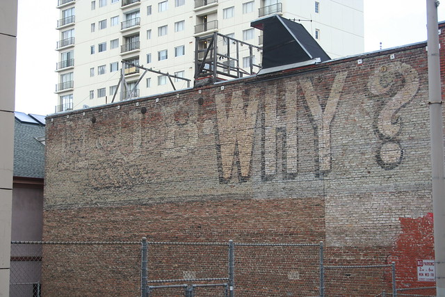 """916 Clay. A sign for MJB Coffee with their classic """"MJB COFFEE WHY?"""" slogan. MJB was one of three major coffee brands founded in San Francisco (the other two being Folgers and Hills Bros.). Founded by Max J. Brandenstein in 1881, the MJB COFFEE WHY? slogan dates to 1910.   Wikipedia  on MJB Coffee. Postcard from the Why? campaign."""