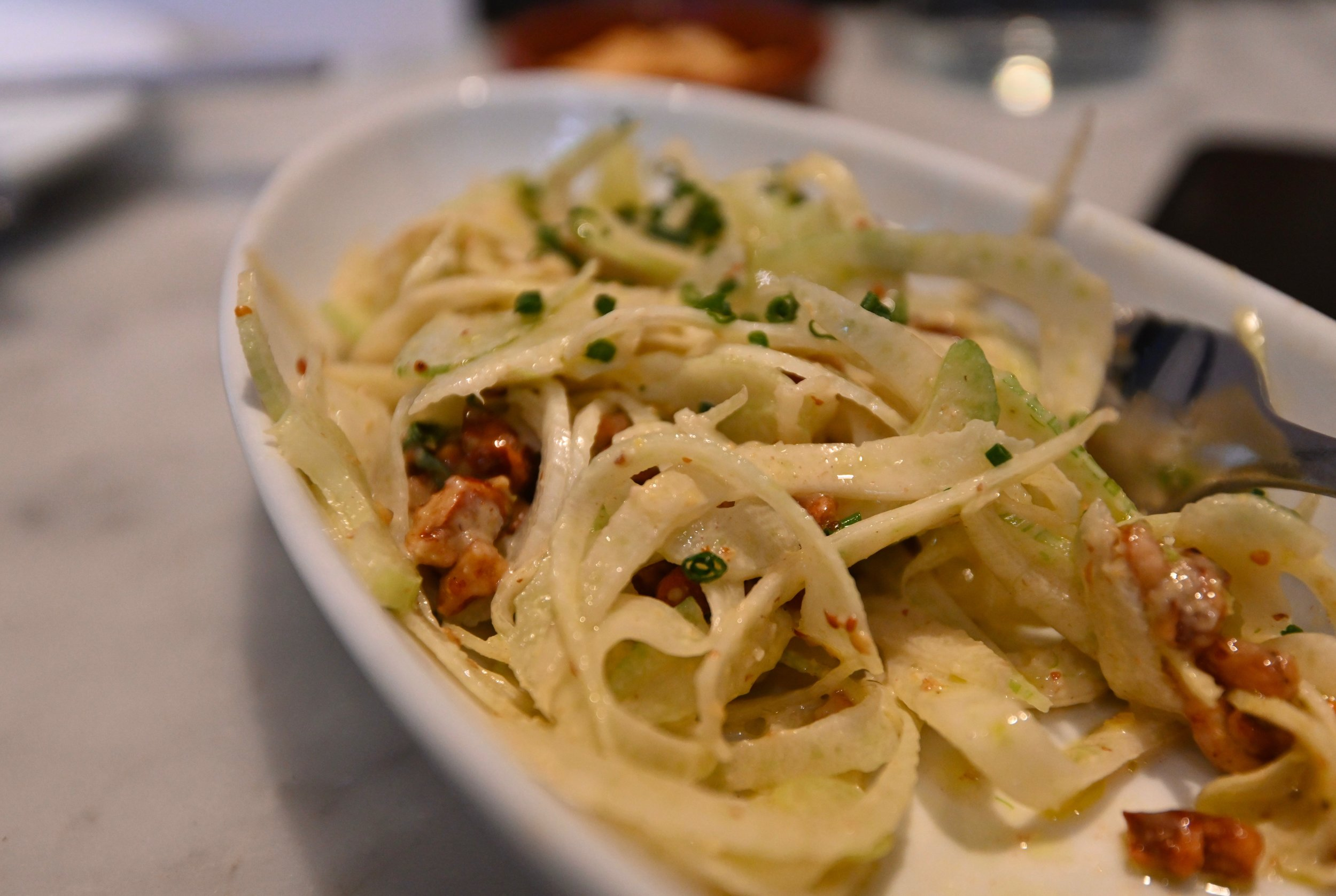 Fennel salad, dressed with a grilled lemon vinaigrette, tarragon and candied pecans.