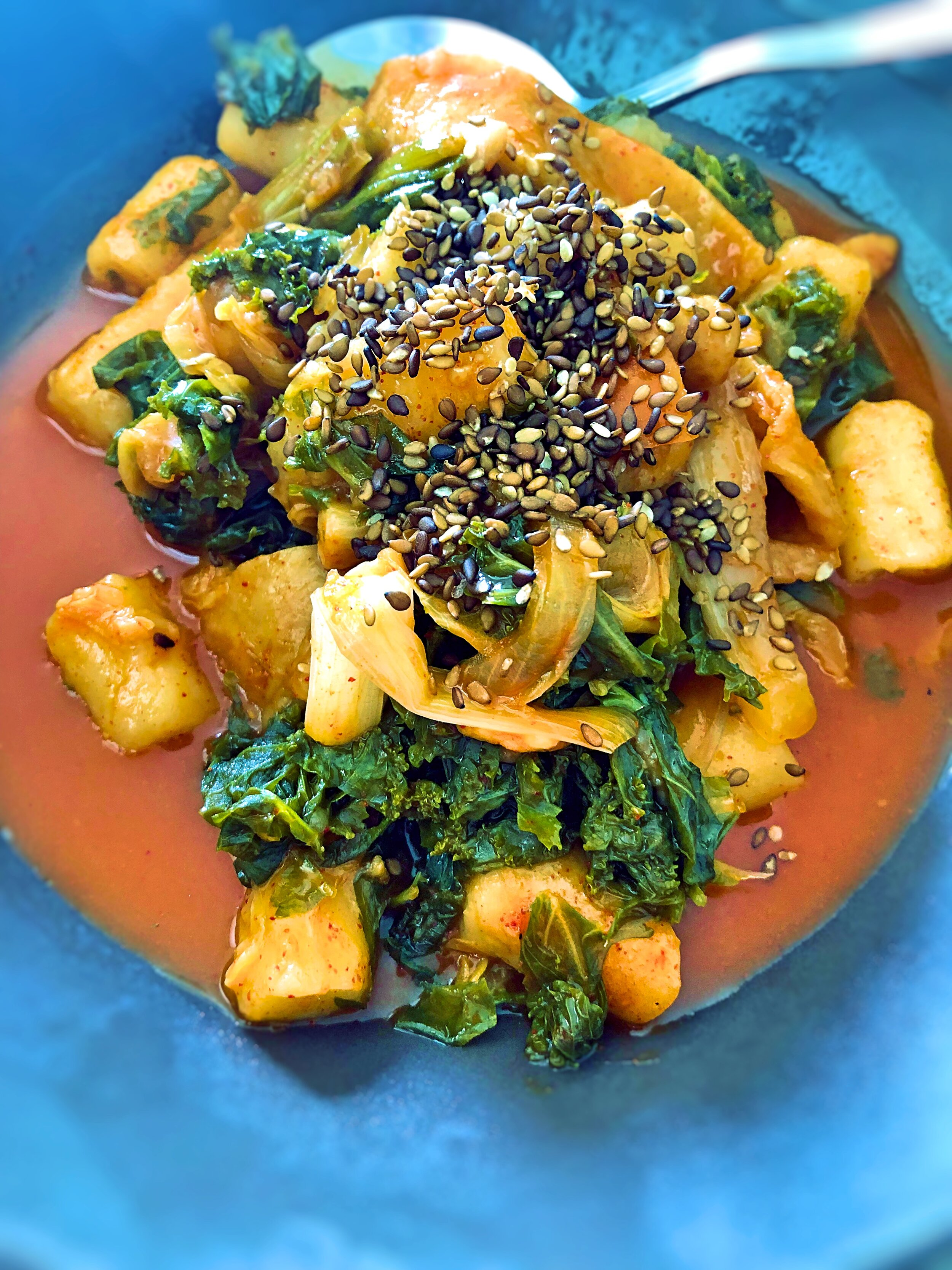Ingredients: Soft or semi-firm Tofu, Western and Chinese Kale, Sesame Seeds, Onions, Sweet chilli sauce, water, S+P, Lime, Cooking oil,  Method: Start by creating the base of this simply soup by caramelising the onions to bring out their natural sweetness, add in the washed chopped greens; the sweet chilli sauce and water - balancing it well with the spices and acids, bring it all to the boil then simmer on low. Add in the soft tofu and gently stir. Top with the crunchy sesame seeds. This dish can also be served over rice or noodles. (you can use gluten free soy sauce or vegan fish sauce here as well)