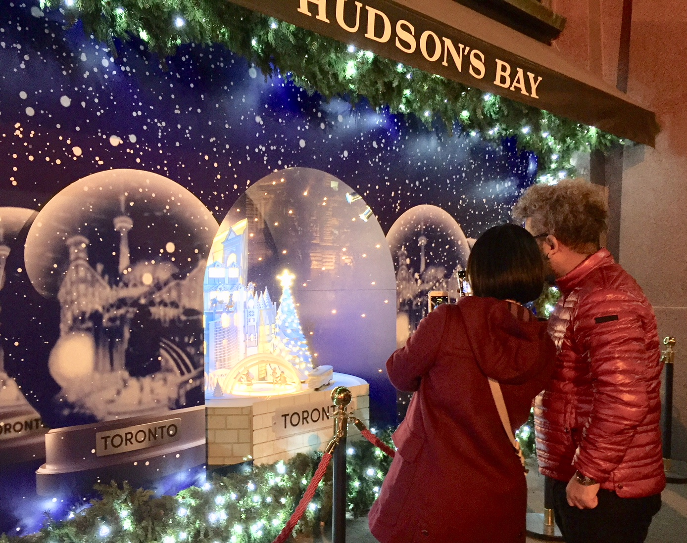 Two people pause to take photos of the Hudson's Bay holiday windows. (Photo: Regina Dickson/CanCulture)