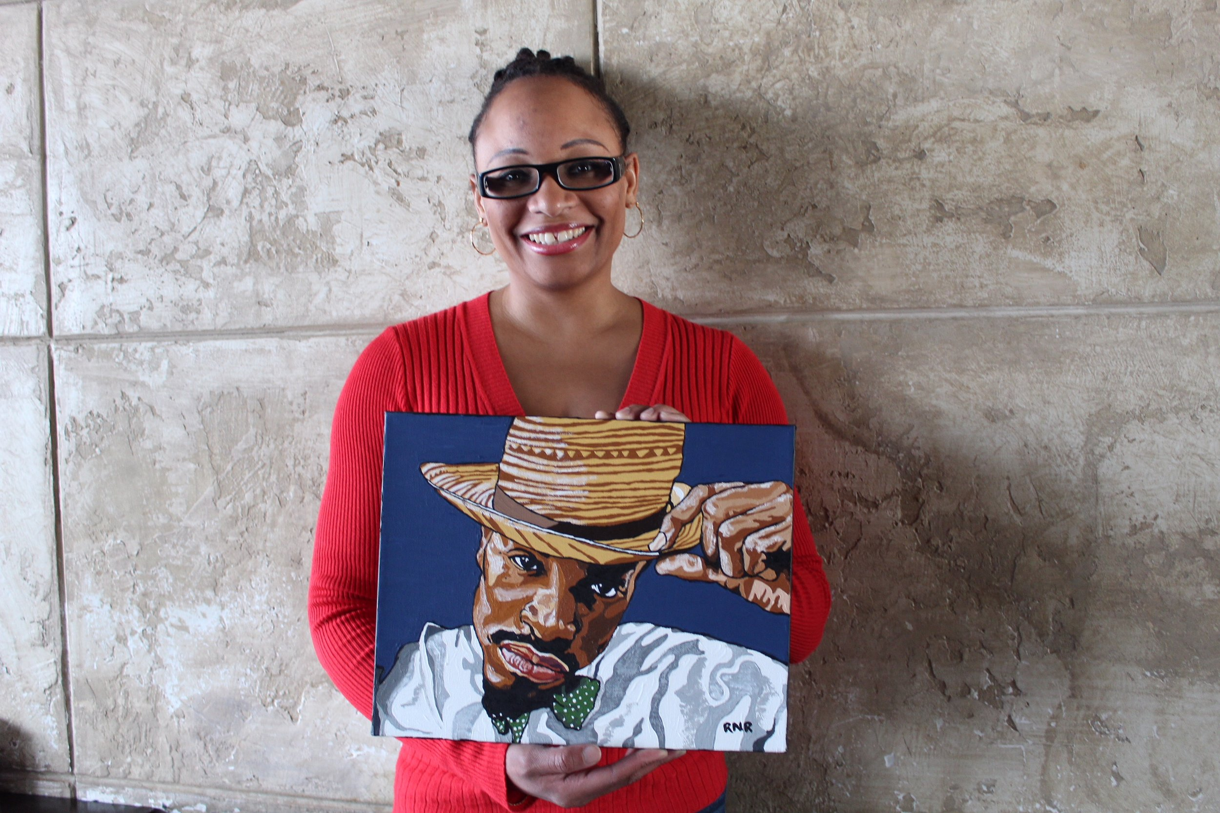 Rawlins holding her painting of Andre 3000, an artist, musician and actor (CanCulture/Madi Wong).