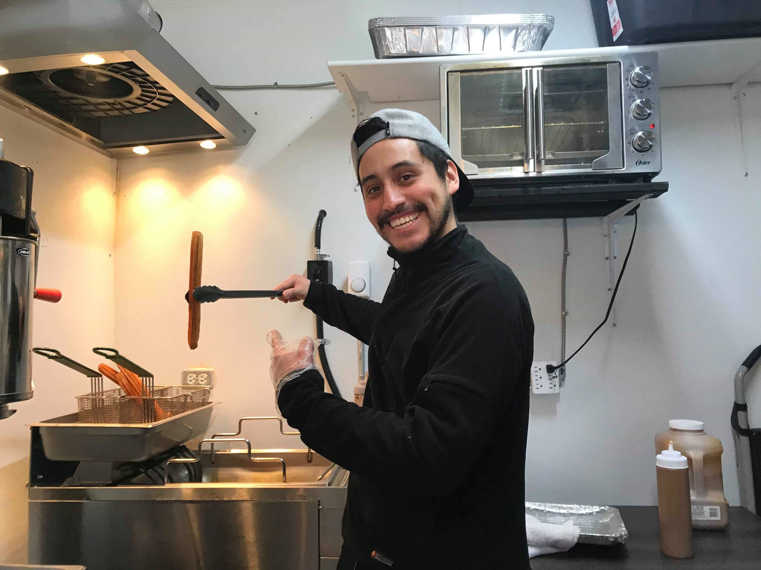 Sergio Herrera making fresh churros inside of the Choco Churros stand. (CanCulture/Keisha Balatbat)