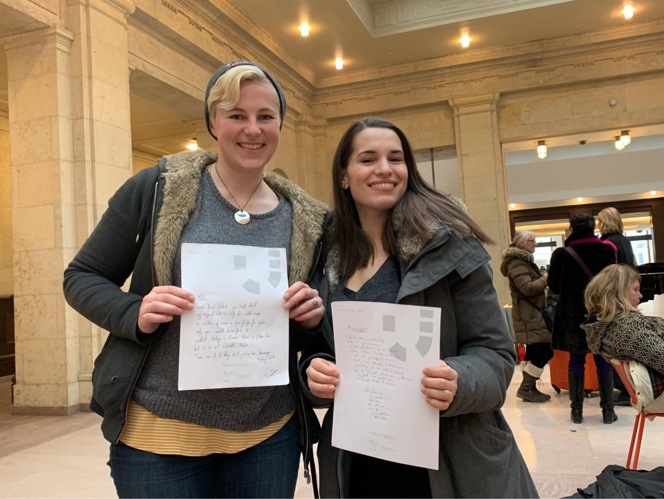 Hannah Martin, left, with her company co-owner Shannon Litt, right, posing with their poems at the event. (CanCulture/Alexander Sowa)