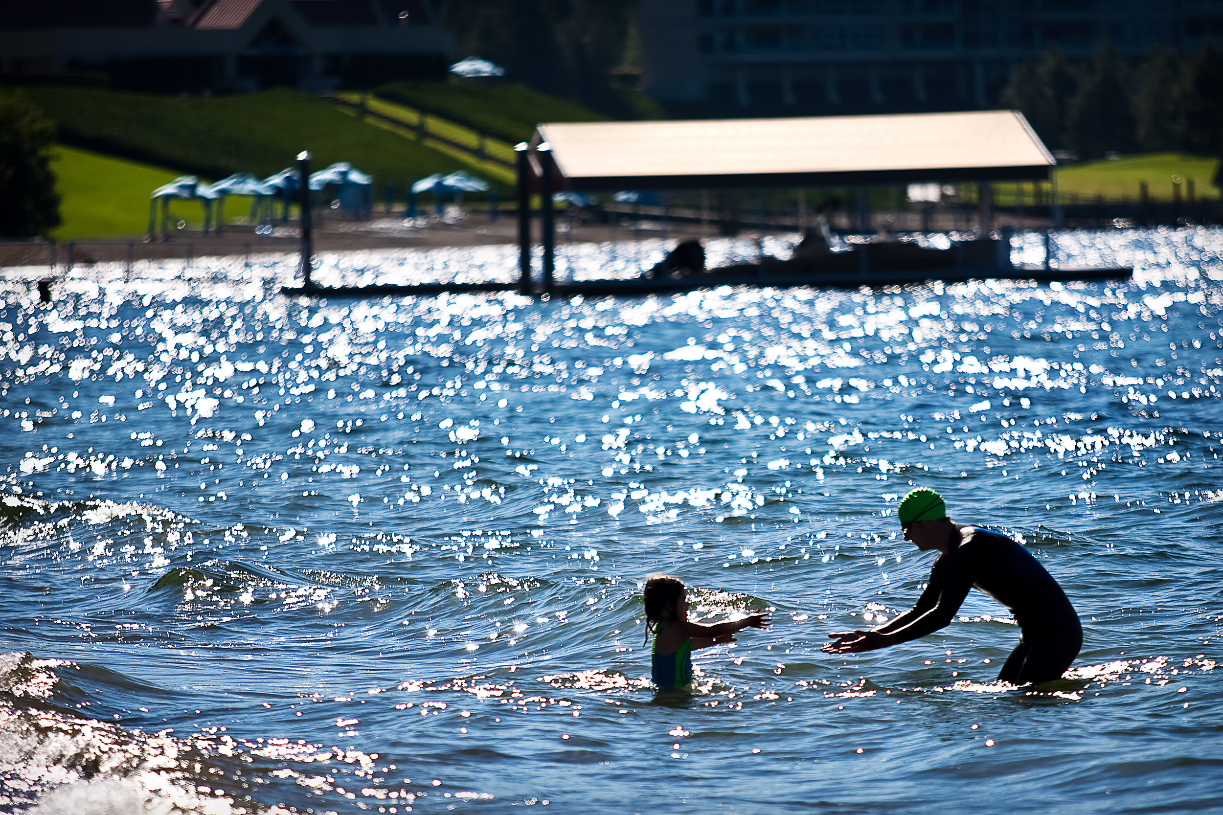 Marcos Donolo of Pullman reaches out to hold his daughter Kiara on Sanders Beach just before the Steve Omi Memorial Swim in Coeur d'Alene on July 18, 2009.