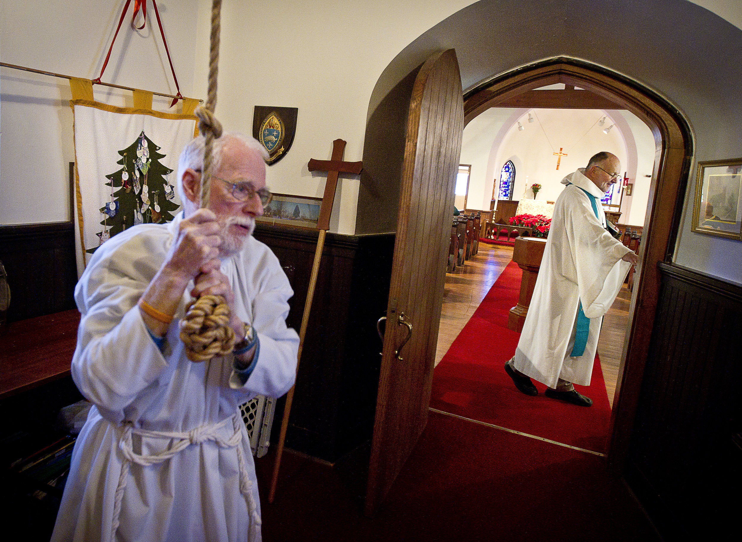 NORTH LAKE, WI — JANUARY 18, 2015: Reverend David Couper prepares for mass as junior warden Peter Buerosse rings the bells at the St. Peter's Episcopal Church, Sunday, January 18, 2015.