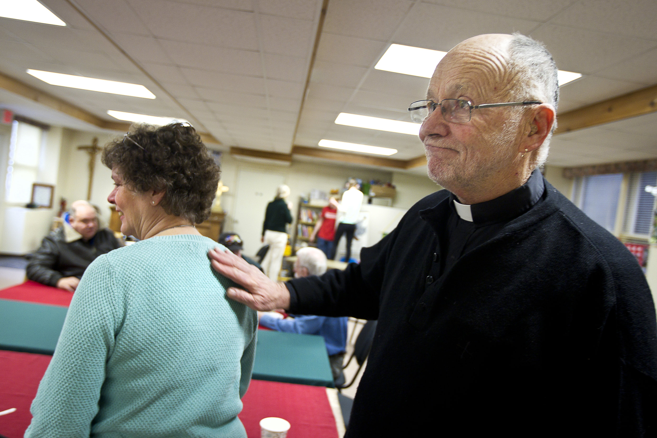NORTH LAKE, WI — JANUARY 18, 2015: Reverend David Couper, right, pats parishioner Mary Buerosse after mass at St. Peter's Episcopal Church, Sunday, January 18, 2015.