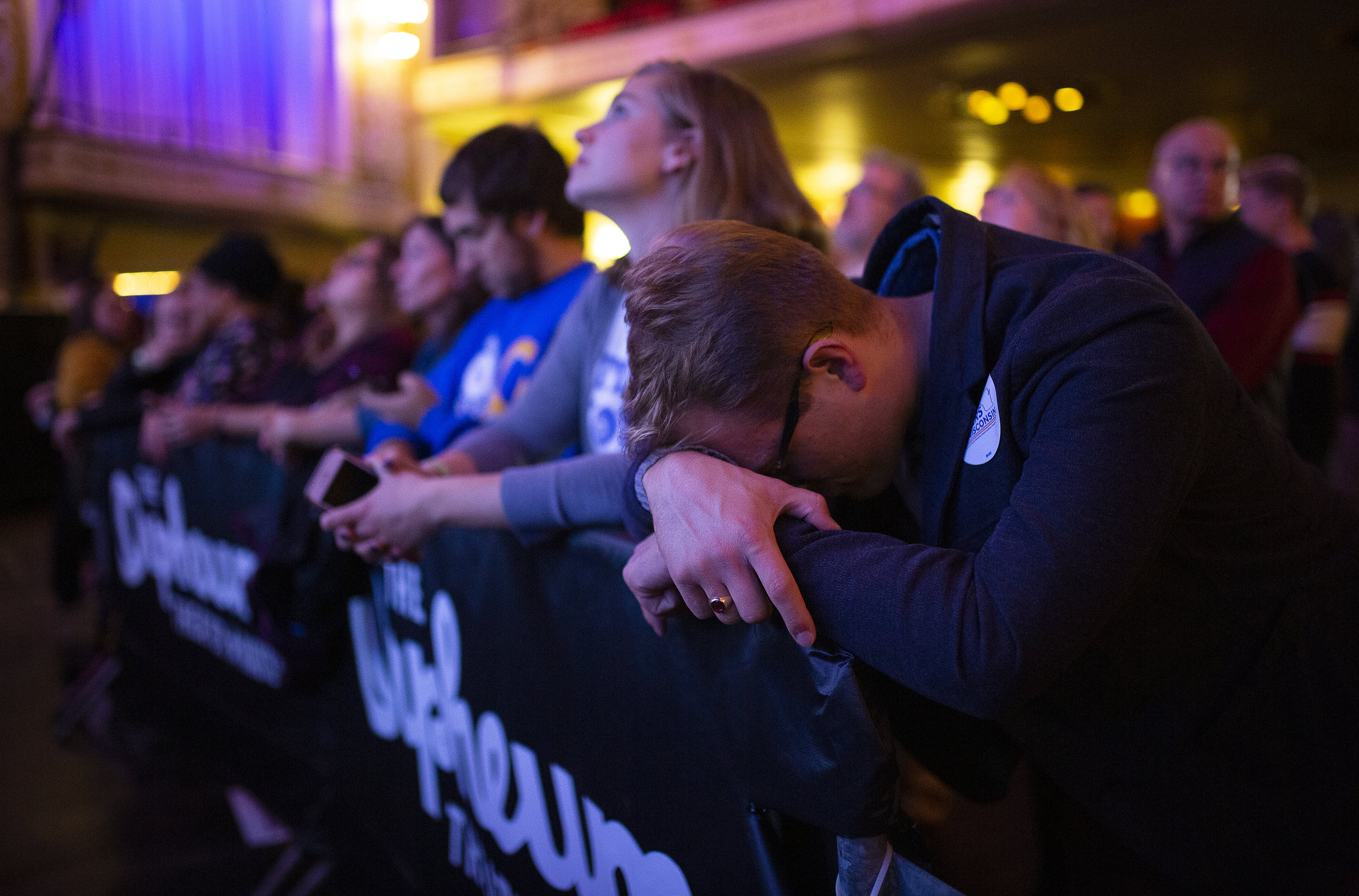 Andrew Carlson rests his head before Tony Evers took the stage during the Election Night watch party at the Orpheum Theater in Madison, Wisconsin, Wednesday, Nov. 7, 2018.