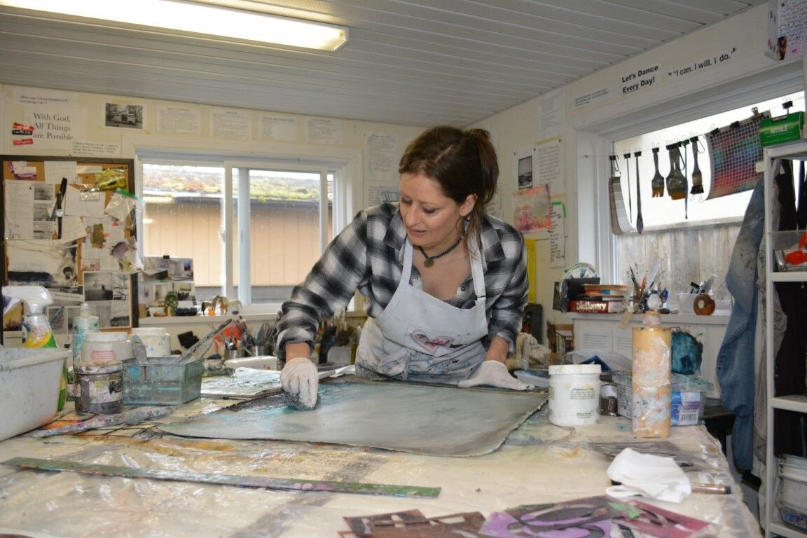 Deb Chaney in her home studio in Coquitlam, BC working on a mixed media painting on paper