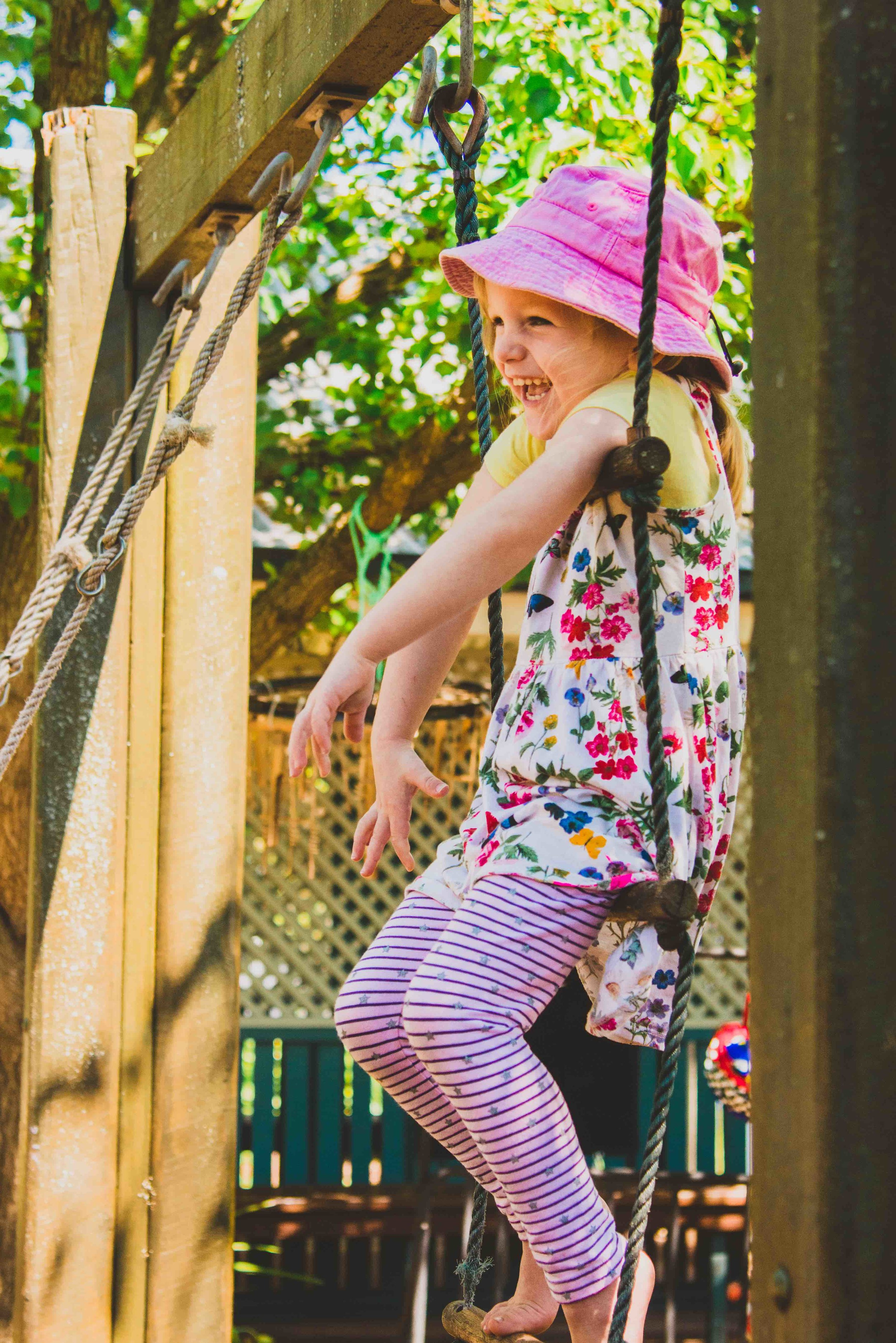Little girl in pink hat laughing with joy on rope ladder