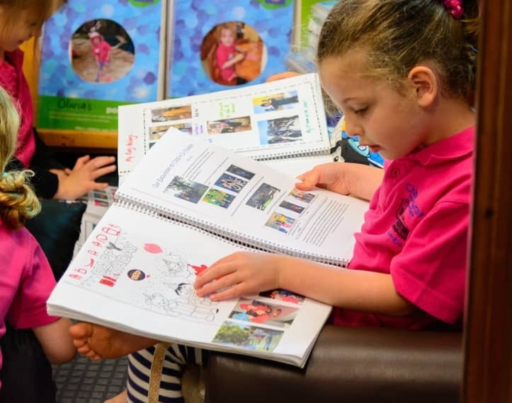 Chiselhurst Kindergarten children reading their personal portfolio capturing their journey at Chiselhurst
