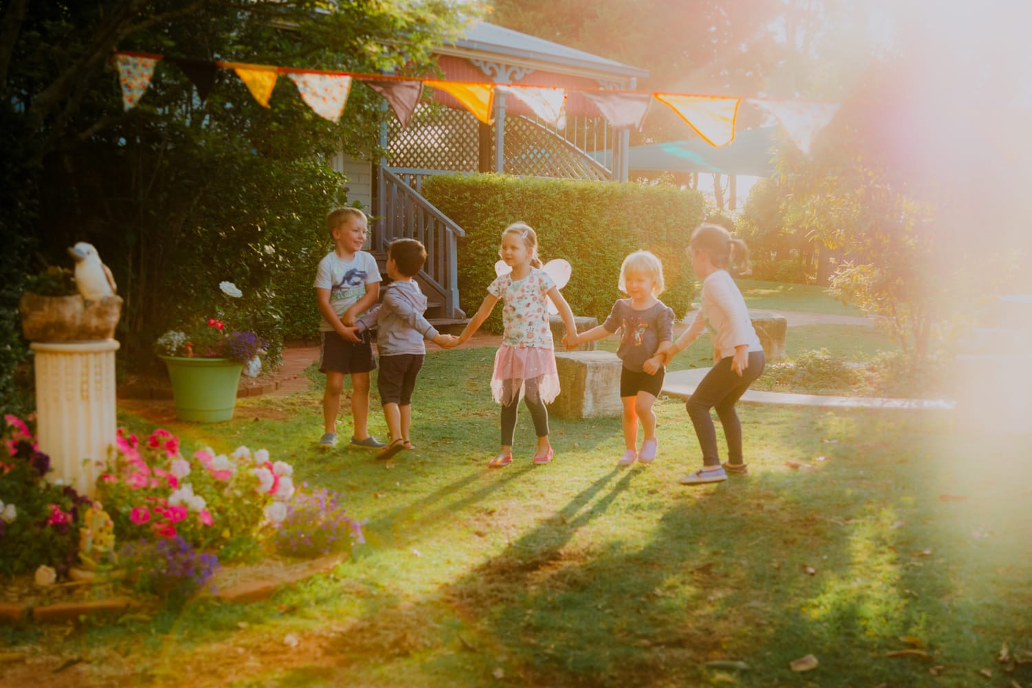 Chiselhurst Kindy Toowoomba front garden in the afternoon children holding hands playing