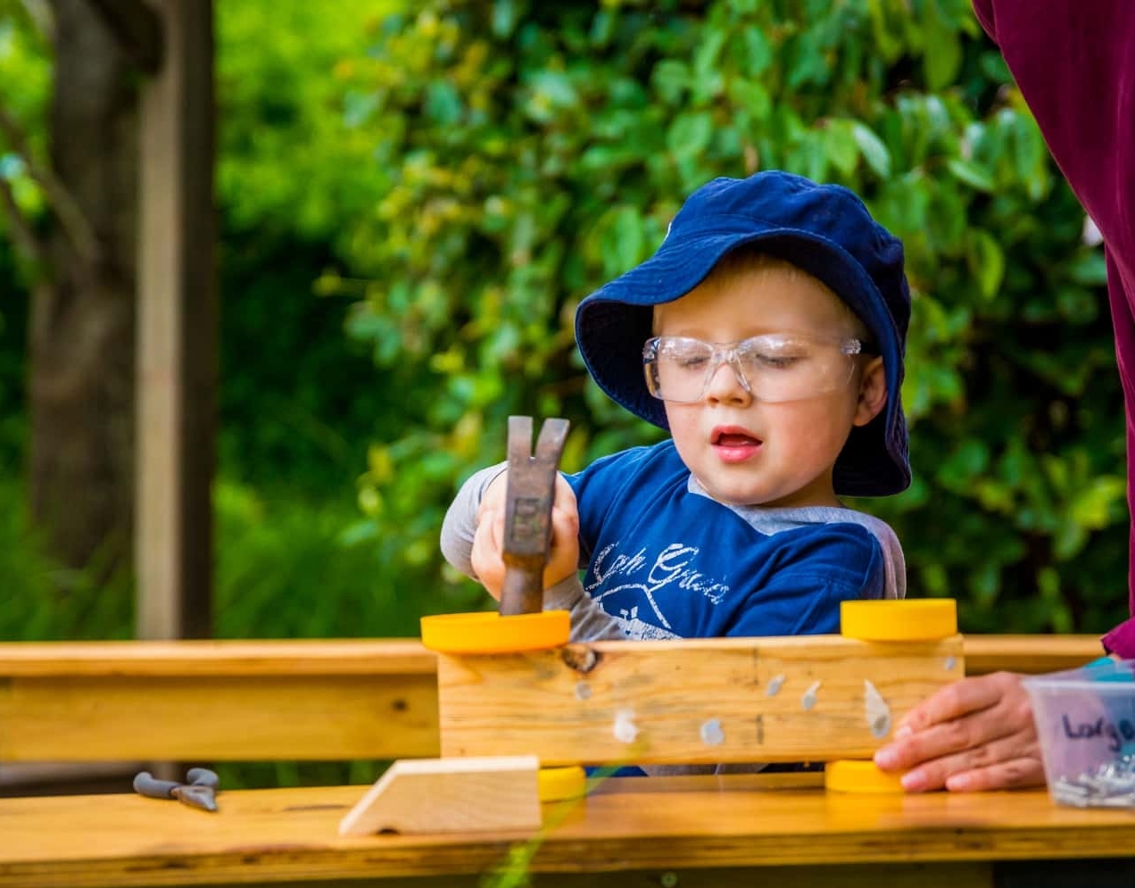 Chiselhurst boy doing woodwork all by himself with educator watching.