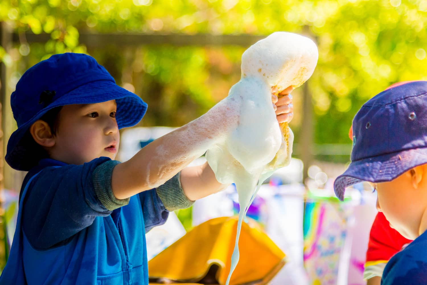 Boy in blue hat playing with water and sponges at Chiselhurst Kindergarten