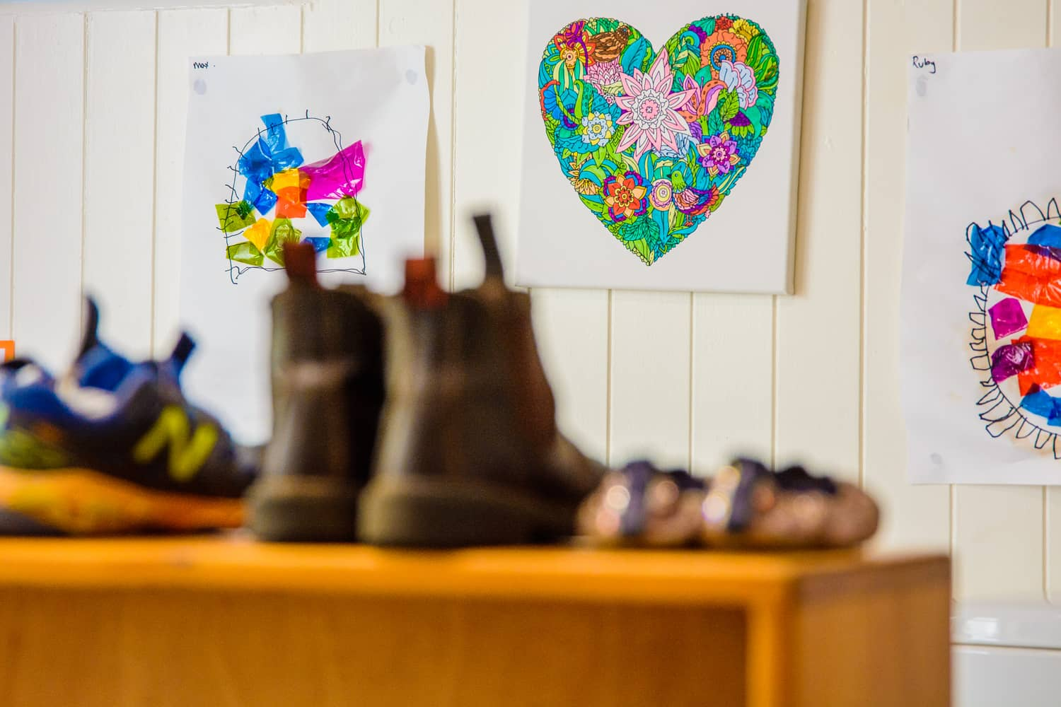 Childrens shoes all lines up and artwork on the wall in the classroom