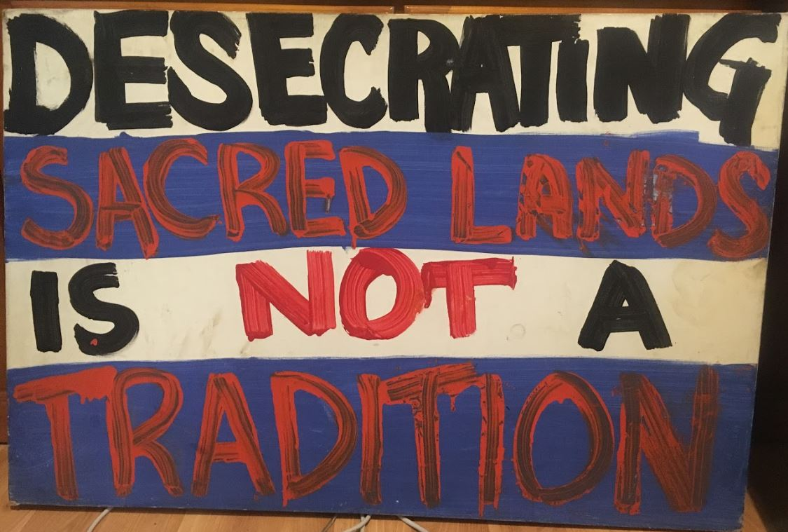 Desecrating Sacred Lands is Not a Tradition - Donated for display from Ruth Aloua.  She first carried this sign on the mauna  on October 7, 2014 . Since this sign has been held through the movement by many protectors and allies, including, Francois Waikoloa (Image Right)..