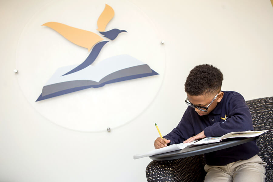 A student sitting, working on a writing assignment, with the Purpose Prep logo on the wall behind him.